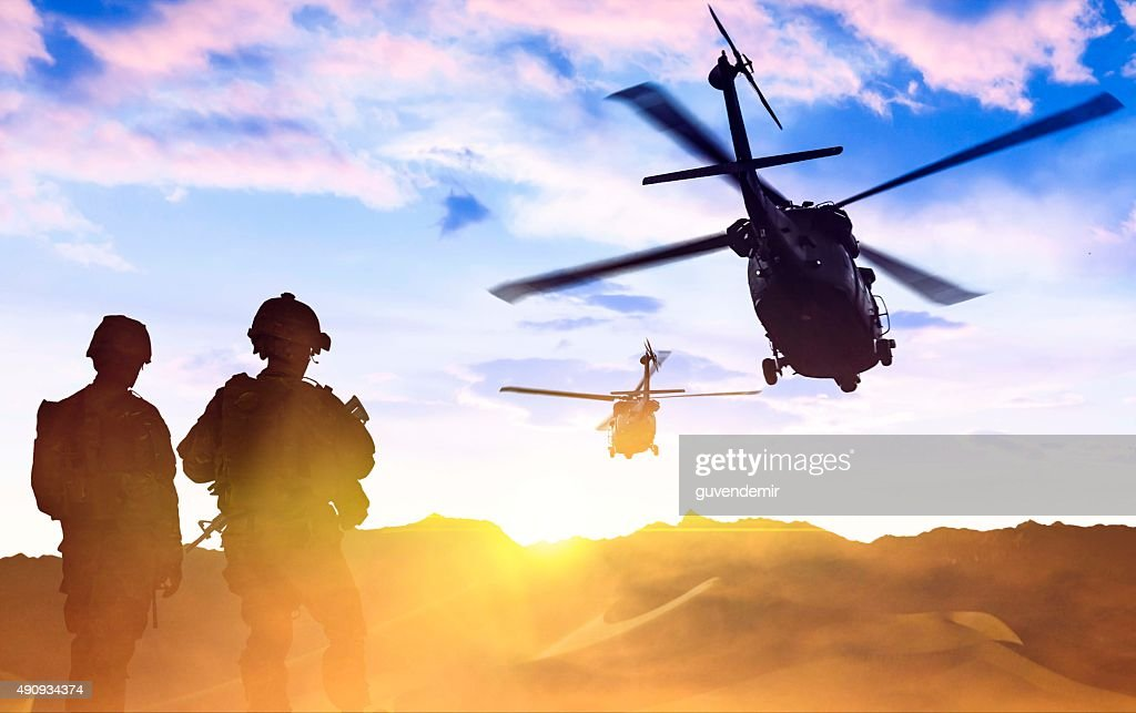 Military Helicopter and Army Soldiers at sunset : Stock Photo