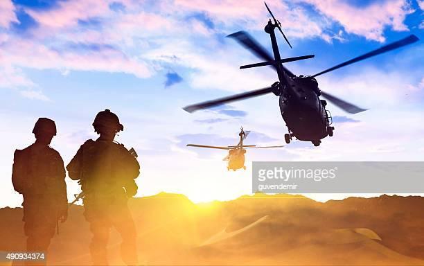 Helicóptero militar y Army Soldiers al atardecer