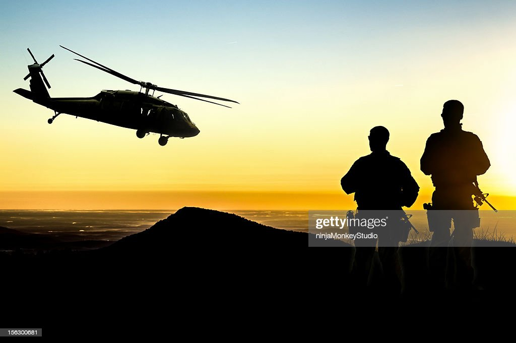 Military Helicopter and Army Soldiers Overlook the Setting Sun : Stock Photo
