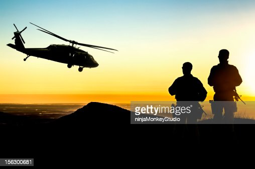 Military Helicopter and Army Soldiers Overlook the Setting Sun