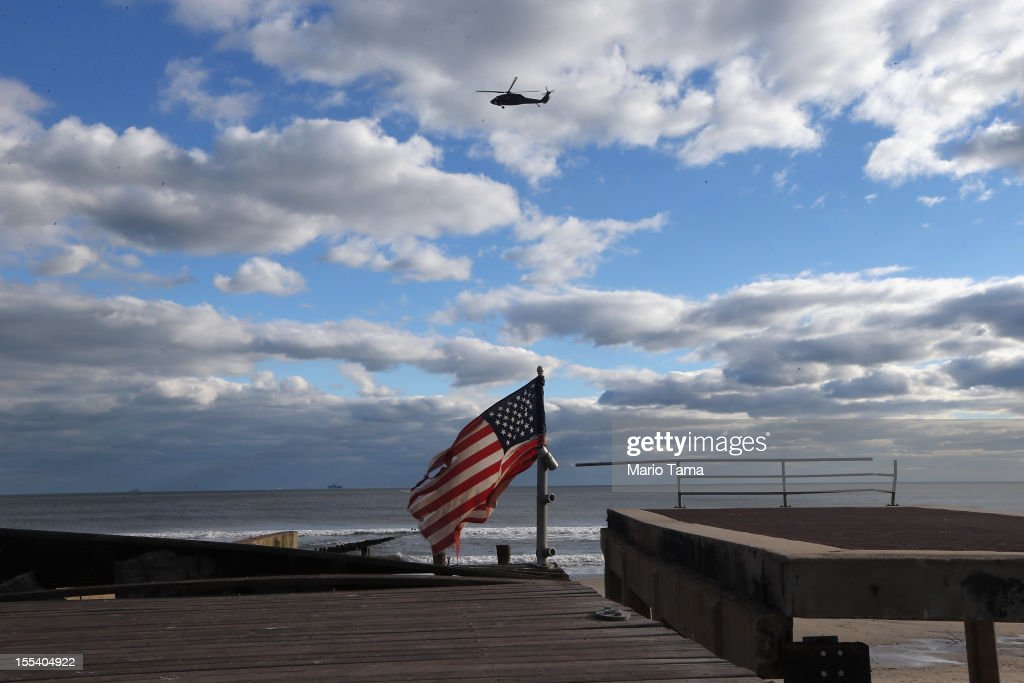 A military helicopter flies above the destroyed boardwalk and a tattered American flag following Superstorm Sandy at Rockaway Beach on November 3, 2012 in the Queens borough of New York City. Most of the Rockaway Peninsula remains without power as colder weather arrives. With the death toll currently over 90 and millions of homes and businesses without power, the US east coast is attempting to recover from the effects of floods, fires and power outages brought on by Superstorm Sandy.