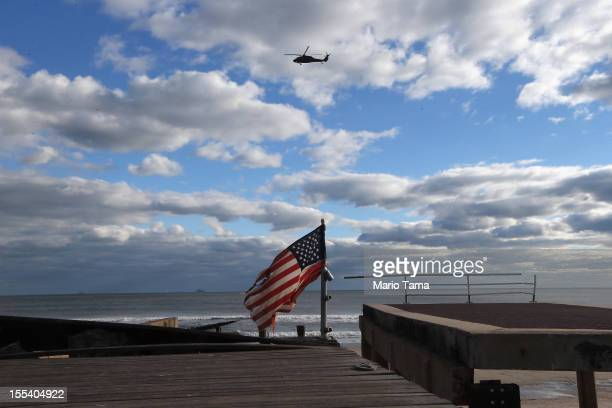 A military helicopter flies above the destroyed boardwalk and a tattered American flag following Superstorm Sandy at Rockaway Beach on November 3...