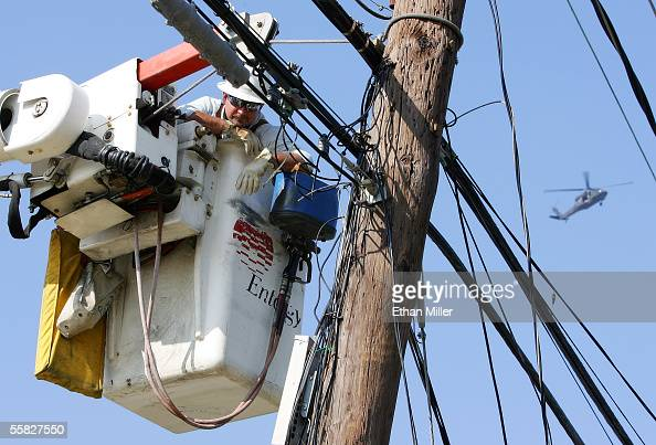 A military helicopter flies by as Entergy Corporation worker Michael 'Flash' Gordon acts as a spotter for other crew members on the ground as they...