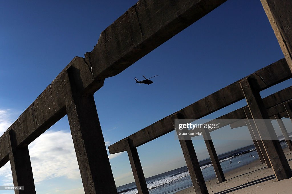 A military helicopter flies over the remaining pillars of the iconic boardwalk in the heavily damaged Rockaway neighborhood where a large section of the boardwalk was washed away on November 14, 2012 in the Queens borough of New York City. Two weeks after Superstorm Sandy slammed into parts of New York and New Jersey, thousands are still without power and heat.