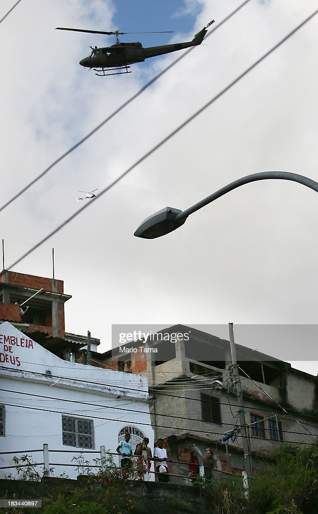 A military helicopter flies overhead during a 'pacification' operation in the favela complex of Lins de Vasconcelos, in the North Zone, on October 6, 2013 in Rio de Janeiro, Brazil. The favela complex, or shanty town, was previously controlled by drug traffickers and will now be occupied by the city's 35th UPP or 'Police Pacification Unit'. The favela pacifications are occurring amid Rio de Janeiro's efforts to improve security ahead of the 2014 FIFA World Cup and 2016 Olympic Games.