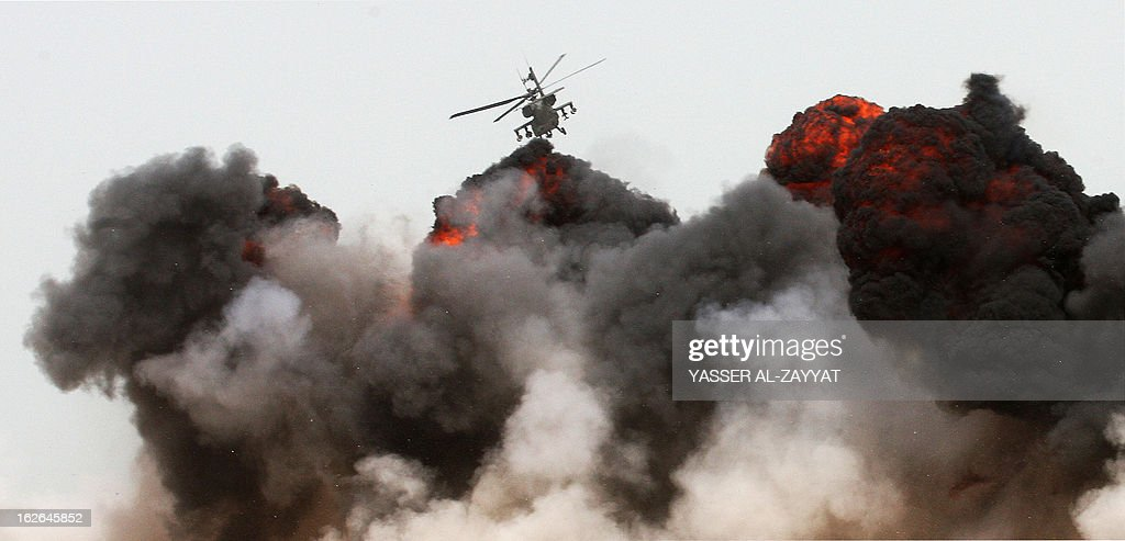 A military helicopter is seen flying over a cloud of smoke during a military show held at Failaka island, about 30 kilometres off the Kuwaiti coast, on February 25,2013, as part of joint Gulf Cooperation Council (GCC) military exercises that took place during celebrations to mark the 52nd Independence Day of the Gulf state and the 22nd anniversary of the end of the Gulf war with the liberation of Kuwait from Iraqi occupation.