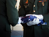 This military honor guard carefully folds the United States flag for presentation to family members at a veteran's funeral. Selective focus on flag and gloved hands. Would make good illustration for U