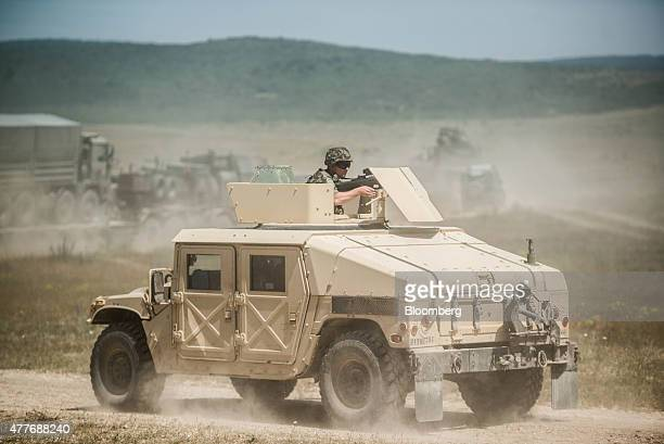 A military Hummer vehicle carries troops in a battlefield maneuver during the Capable Logistician field training exercise by the North Atlantic...