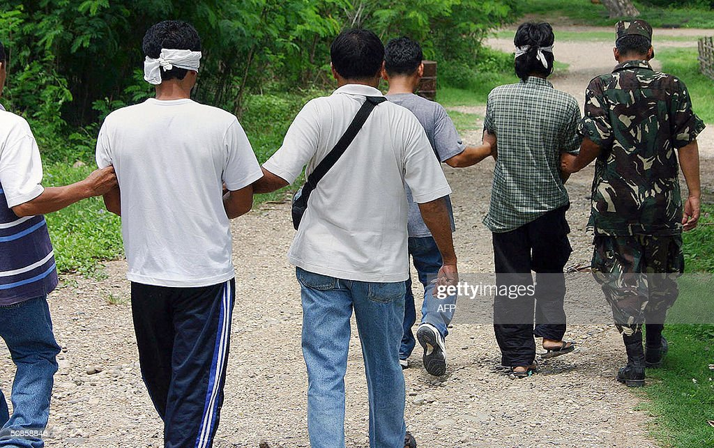 Military intelligence personnel escort alleged Abu Sayyaf leader Usman Lijal (L) and bodyguard Allimudin Addala (R) at a military camp in southern Zamboanga city 20 May 2004 following their arrest. Lijal linked by authorities to the abduction of a group of Filipinos and western tourists including three Americans in May 2001 were captured together during a raid in his hideout. Manila and Washington have linked Abu Sayyaf group to Osama bin Laden's al-Qaeda network.