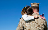 Military man hugs his child