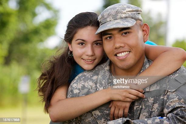 Military man in his uniform hugging a woman