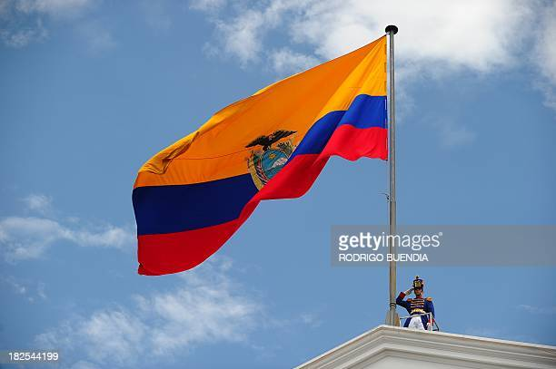A military member salutes alongisde an Ecuadorean flag as President Rafael Correa takes part in a ceremony honouring those that died during a police...