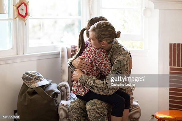 Military Mom hugging daugher at home