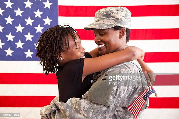 Military mom welcomed home by daughter. USA flag. Army veteran.
