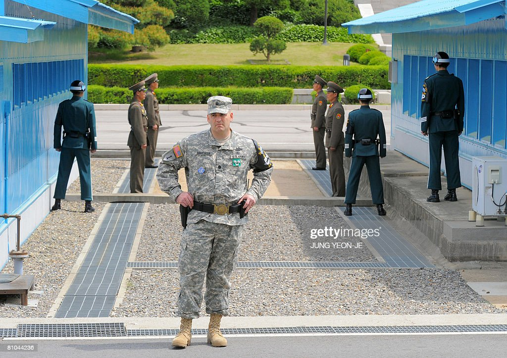 A US military officer (C) is seen as South and North Korean soldiers stand guard at a joint security area known as Panmunjom in the Demilitarized Zone dividing the two Koreas on May 10, 2008. A US envoy crossed the inter-Korean border into South Korea, bringing with him documents about North Korea's nuclear activities as part of efforts to disarm the communist state.