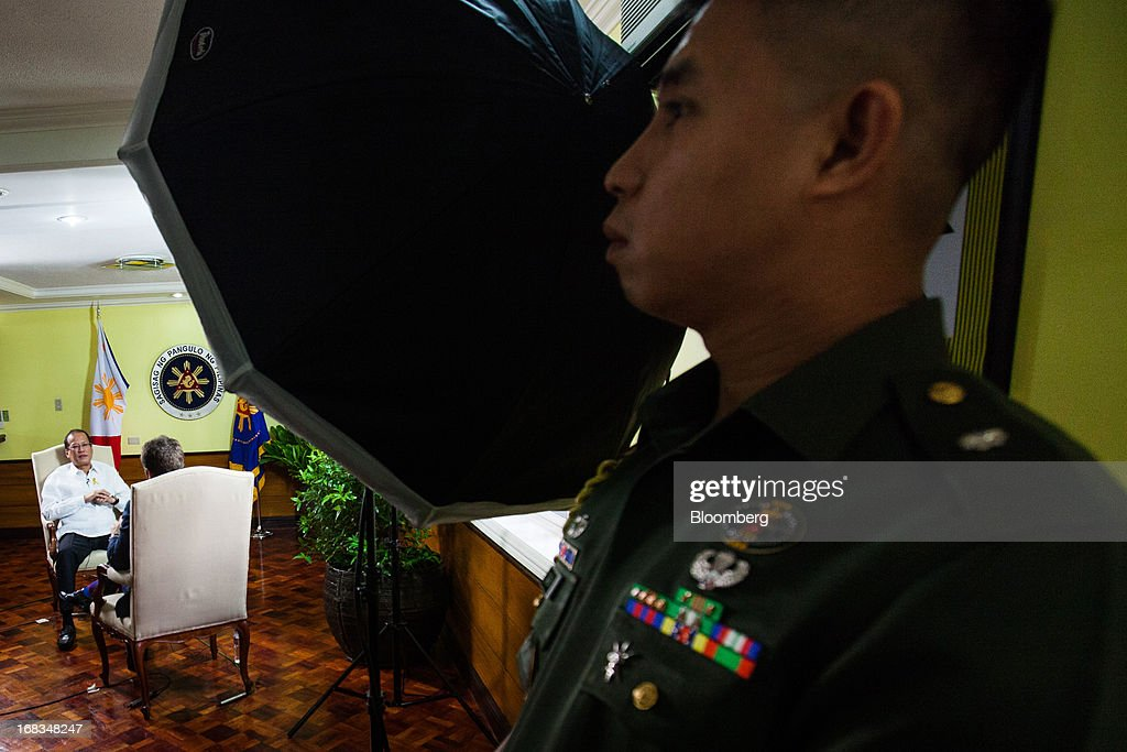 A military officer, right, observes as Benigno Aquino, the Philippines' president, left, speaks during an interview in the Malacanang Palace compound in Manila, the Philippines, on Wednesday, May 8, 2013. The Philippines, Asia's fastest-growing economy after China, needs to do more to finally lose its decades-old tag as the 'Sick Man of Asia,' according to Aquino. Photographer: Julian Abram Wainwright/Bloomberg via Getty Images