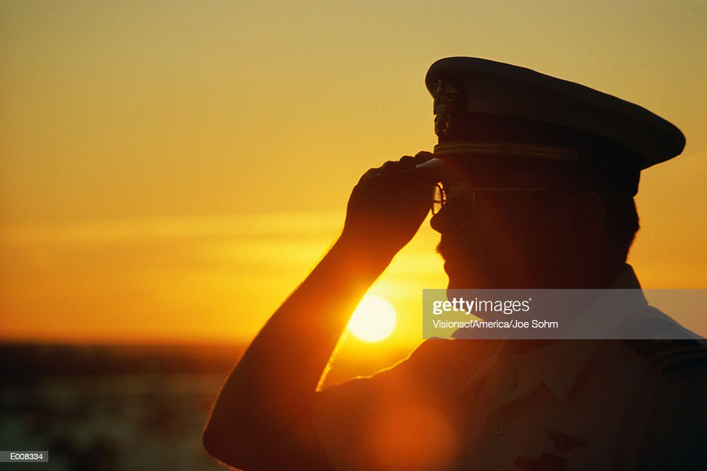 Military officer saluting at sunset : Stock Photo