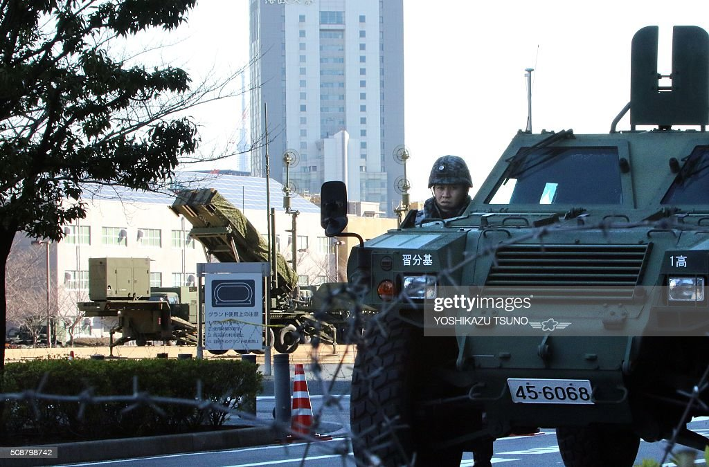 A military officer stands by near a Japanese Self-Defense Force Patriot Advanced Capability-3 (PAC-3) interceptors launcher (L) deployed at the Defence Ministry headquarters in Tokyo on February 7, 2016. North Korea launched a long-range rocket on February 7, violating UN resolutions and doubling down against an international community already determined to punish Pyongyang for a nuclear test last month. AFP PHOTO / Yoshikazu TSUNO / AFP / YOSHIKAZU TSUNO