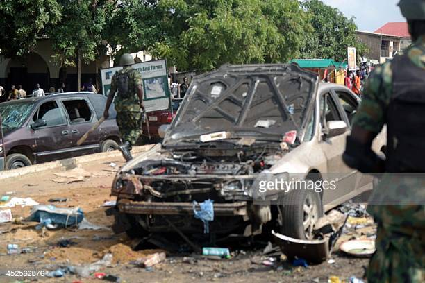 Military officers walk past a scene where a bomb exploded on July 23 2014 in Kaduna north of Nigeria A second blast today in the city has killed at...