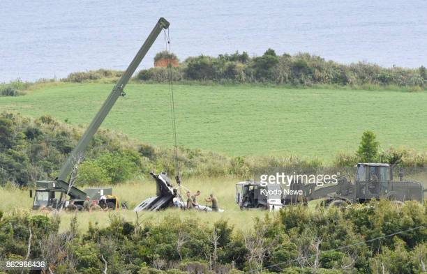 US military officials work in the village of Higashi Okinawa Prefecture on Oct 19 to remove the wreckage of a CH53E transport helicopter that crash...
