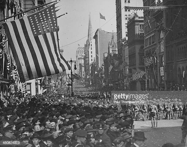 A military parade with crowds of excited spectators along 5th Avenue in celebration of Armistice day and peace in Europe following World War One New...