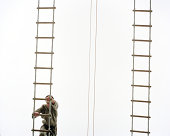 Military person climbing rope ladder