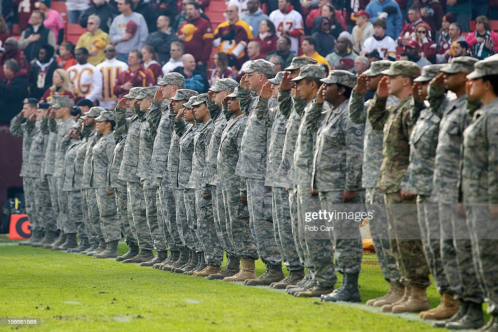 Military personal salute during the playing of the national anthem before the start of the Washington Redskins and Philadelphia Eagles game at FedEx Field on November 18, 2012 in Washington, DC.
