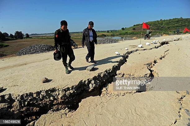A military personnel and a Myanmar man look a crack in the road in Sintgu township Mandalay division in central Myanmar on November 12 2012 Myanmar...