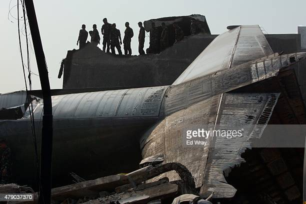 Military personnel and search and rescue teams comb through the wreckage of a military transport plane which crashed into a building on June 30 2015...
