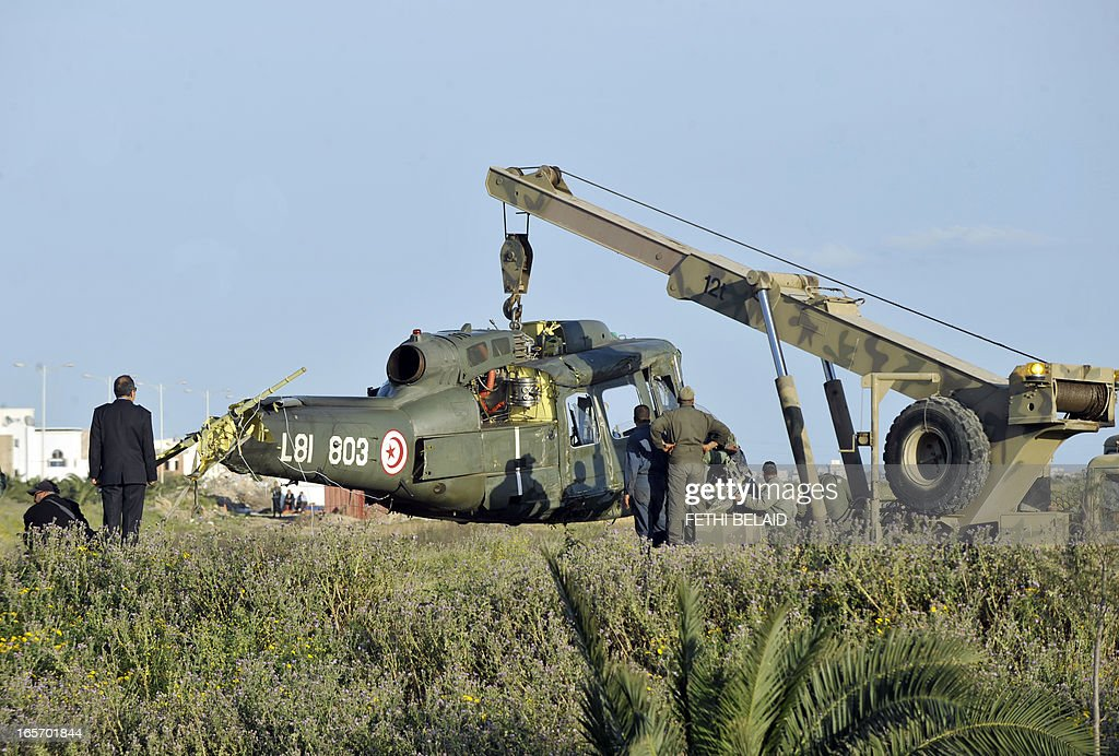 Military personnel clear the debris of a Tunisian military helicopter at the site of it's crash landing near an air base in the capital's suburb of Aouina on April 5, 2013. The crash left two people injured, a defence ministry spokesman told AFP.