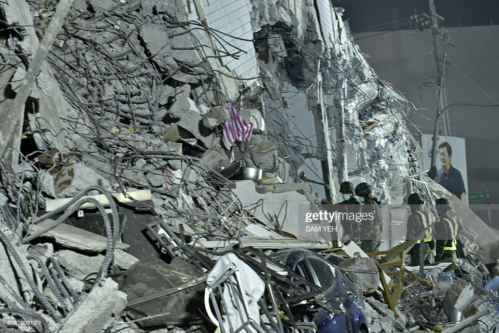Military personnel conduct rescue work at the site of a collapsed building in the southern Taiwanese city of Tainan on February 6, 2016 following a strong 6.4-magnitude earthquake. A powerful earthquake in Taiwan felled a 16-storey apartment complex full of families who had gathered for Lunar New Year celebrations in the early hours of February 6, with at least seven dead and more than 30 feared trapped. AFP PHOTO / Sam Yeh / AFP / SAM YEH