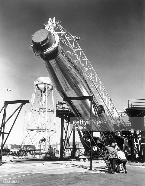Military personnel erect an Atlas ICBM on the launching into firing position
