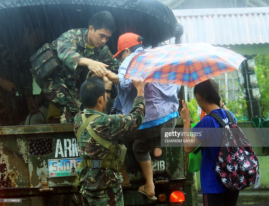 Military personnel evacuate residents from a village in the city of Legaspi in Albay province south of Manila on December 14 as typhoon Melor...
