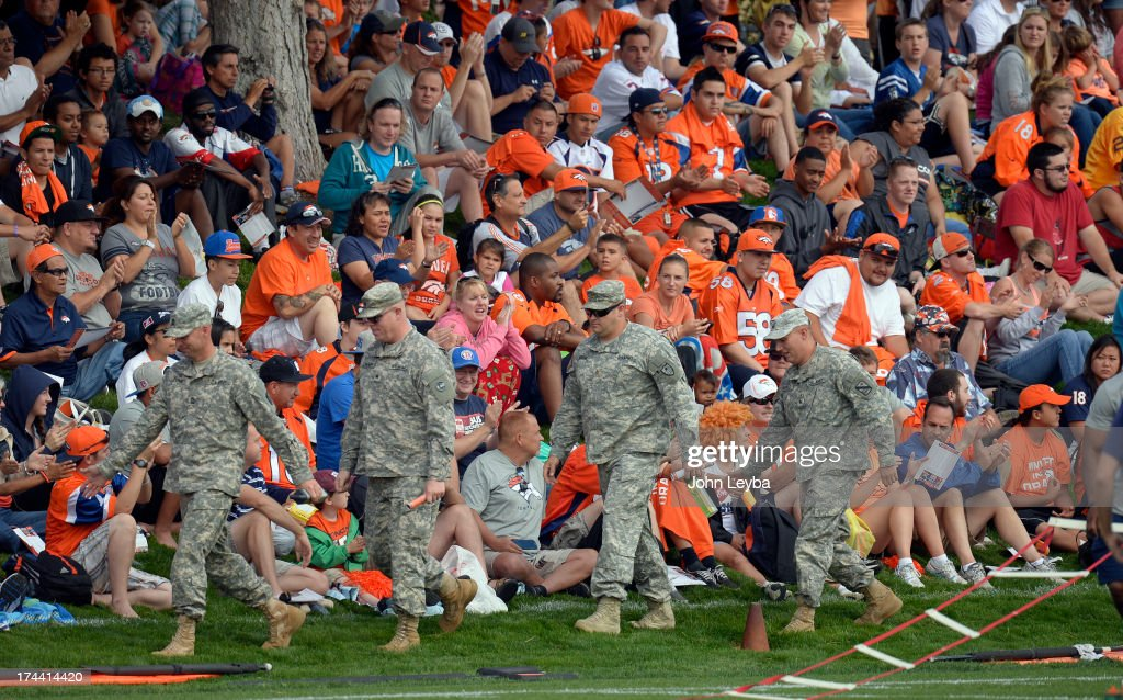 Military personnel get high fives from crowd as they attend the Denver Broncos practice during opening day of training camp July 25, 2013 at Dove Valley.