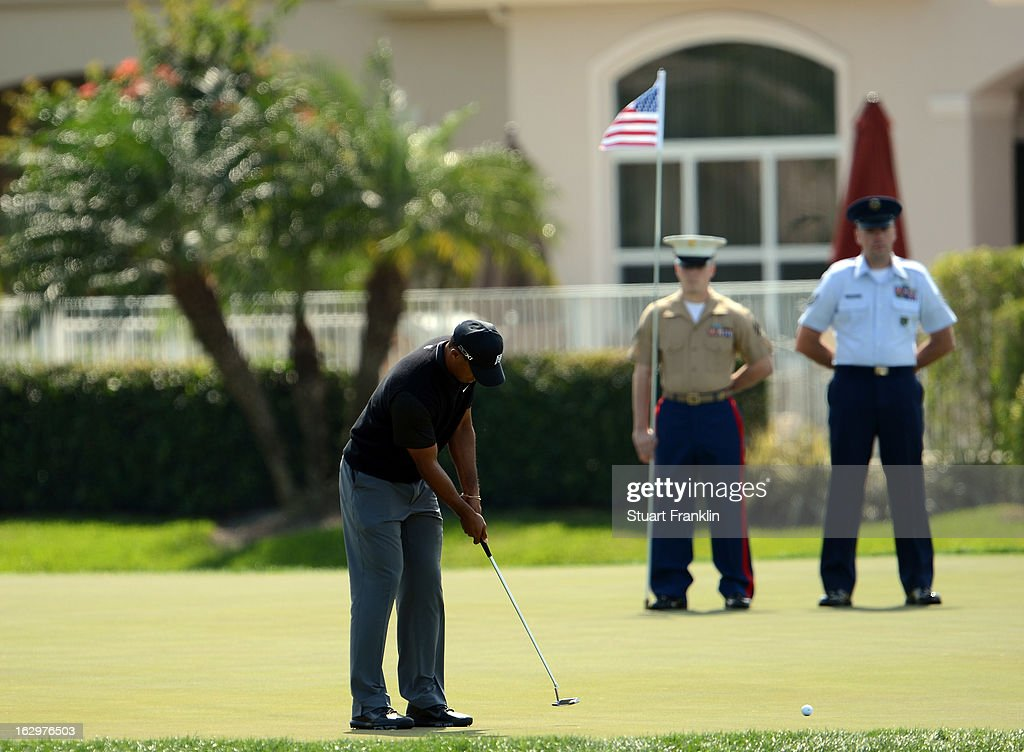 US military personnel hold the stars and stripes flag on the 17th hole as <a gi-track='captionPersonalityLinkClicked' href=/galleries/search?phrase=Tiger+Woods&family=editorial&specificpeople=157537 ng-click='$event.stopPropagation()'>Tiger Woods</a> of USA putts during the third round of the Honda Classic on March 2, 2013 in Palm Beach Gardens, Florida.