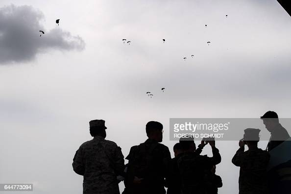 TOPSHOT US military personnel look up at infantry soldiers gliding down in parachutes during a live fire military display in Nakhon Ratchasima in...