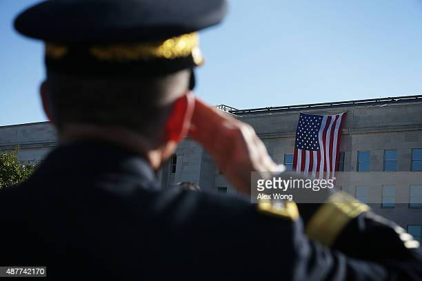 A military personnel salutes during an observance ceremony at the Pentagon Memorial September 11 2015 in Arlington Virginia The nation remembered the...