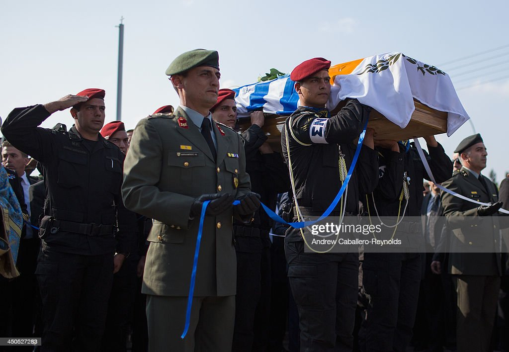 Military personnel stand at attention with the coffin of the Former Cypriot President Glafcos Clerides as it is carried to a church for his funeral service on November 19, 2013 in Nicosia, Cyprus. The Former President, who oversaw his country's entry into the EU in 2004, died in a Nicosia hospital on Friday evening at the age of 94.