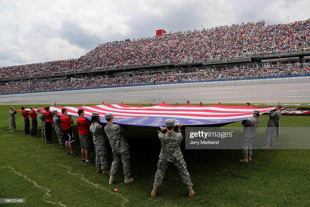 Military Personnel stretch a giant American FLag across the infield during the performance of the National Anthem prior to the start of the NASCAR Sprint Cup Series Aaron's 499 at Talladega Superspeedway on May 5, 2013 in Talladega, Alabama.
