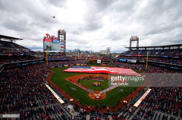 A military plane flies over during the national anthem before an opening day game between the Philadelphia Phillies the Washington Nationals at...