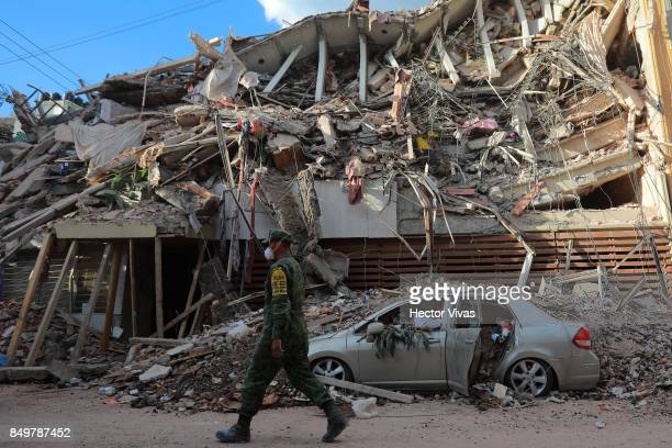 A military police guards a building knocked down by a magnitude 71 earthquake that jolted central Mexico damaging buildings knocking out power and...