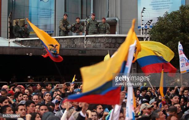 Military police officers guard atop a terrace as supporters of Ecuadorean presidential candidate for the CREO party Guillermo Lasso gather outside...