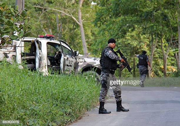 Military police officers track for fugitives of the Anisio Jobim Penitentiary Complex after a riot in the prison left at least 60 people killed and...