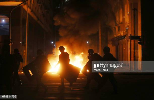 Military Police officers walk past a fire by protestors during a nationwide general strike on April 28 2017 in Rio de Janeiro Brazil The general...