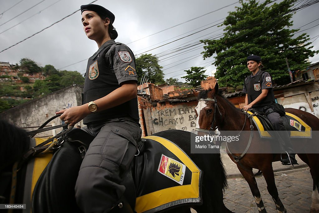 Military police on horseback patrol during a 'pacification' operation in the favela complex of Lins de Vasconcelos, in the North Zone, on October 6, 2013 in Rio de Janeiro, Brazil. The favela complex, or shanty town, was previously controlled by drug traffickers and will now be occupied by the city's 35th UPP or 'Police Pacification Unit'. The favela pacifications are occurring amid Rio de Janeiro's efforts to improve security ahead of the 2014 FIFA World Cup and 2016 Olympic Games.