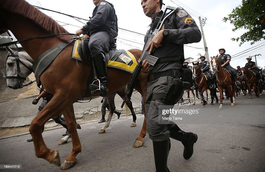 Military police on horseback patrol near the favela complex of Lins de Vasconcelos, in the North Zone, on the day of a 'pacification' operation on October 6, 2013 in Rio de Janeiro, Brazil. The favela complex, or shanty town, was previously controlled by drug traffickers and will now be occupied by the city's 35th UPP or 'Police Pacification Unit'. The favela pacifications are occurring amid Rio de Janeiro's efforts to improve security ahead of the 2014 FIFA World Cup and 2016 Olympic Games.