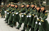 Military police patrol outside the Great Hall of the People before the opening session at the 11th National Committee of the Chinese People's...
