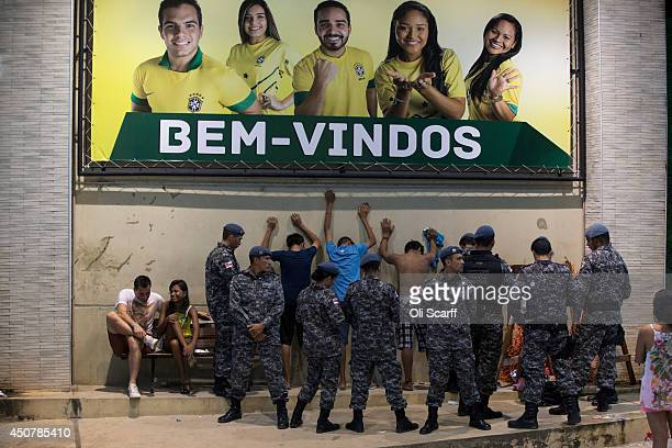 Military police search young men outside the Fan Fest area in Porta Negro under a large sign that reads 'Welcome' June 17 2014 in Manaus Brazil...