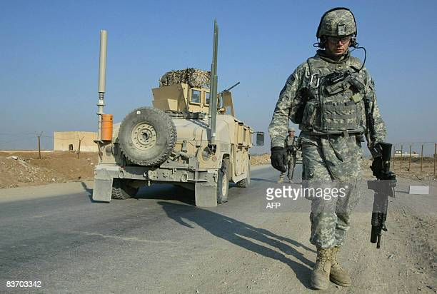 US Military police stop to change the flat tire of their armoured personnel carrier after being hit by a roadside bomb in the Iraqi city of Mosul...
