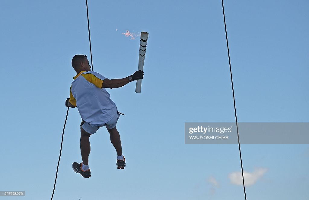 Military policemam torchbearer Manoel Costa descends from the Juscelino Kubitschek bridge in Brasilia, on May 3, 2016. Embattled President Dilma Rousseff greeted the Olympic flame in Brazil on Tuesday, promising not to allow a raging political crisis, which could see her suspended within days, to spoil the Rio Games. The torch will now be carried in a relay by 12,000 people through 329 cities, ending in Rio's Maracana stadium on August 5 for the opening ceremony. / AFP / YASUYOSHI